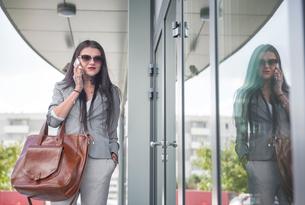Businesswoman walking beside office building, using smartphoneの写真素材 [FYI03596166]