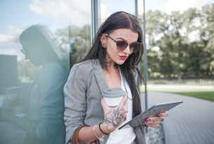 Businesswoman outdoors, holding coffee cup and digital tablet, tattoos on handsの写真素材 [FYI03596167]