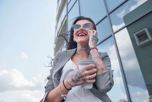 Businesswoman  walking outdoors, holding coffee, using smartphone, tattoos on hands, low angle viewの写真素材 [FYI03596168]