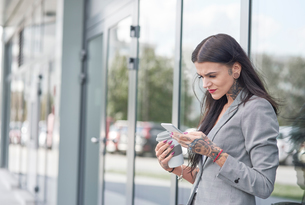Businesswoman outdoors, holding coffee cup and smartphone, tattoos on handsの写真素材 [FYI03596169]