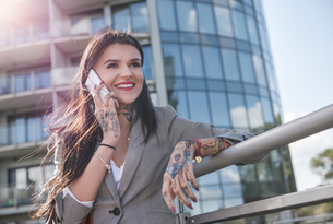 Businesswoman outdoors, using smartphone, smiling, tattoos on handsの写真素材 [FYI03596170]