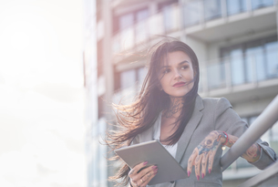 Businesswoman outdoors, holding digital tablet, tattoos on handsの写真素材 [FYI03596171]