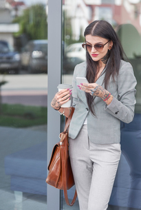 Businesswoman outdoors, holding coffee cup, using smartphone, tattoos on handsの写真素材 [FYI03596172]
