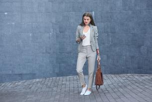 Businesswoman outdoors, using smartphoneの写真素材 [FYI03596175]