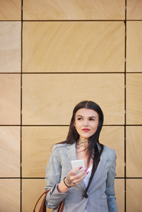 Businesswoman outdoors, using smartphoneの写真素材 [FYI03596176]