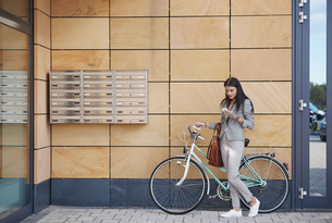 Businesswoman beside office building, walking bicycle, using smartphoneの写真素材 [FYI03596179]