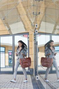 Businesswoman walking outdoors, using smartphoneの写真素材 [FYI03596180]