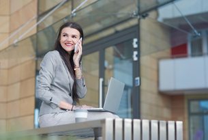 Businesswoman sitting outdoors, using laptop, holding smartphone to ear, smilingの写真素材 [FYI03596181]