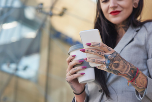 Businesswoman outdoors, holding coffee cup, using smartphone, tattoos on hands, mid sectionの写真素材 [FYI03596184]