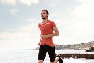 Young male runner running along beachの写真素材 [FYI03596236]