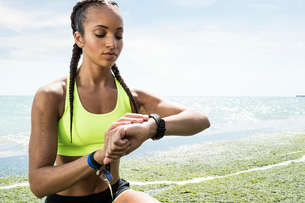 Young woman beside sea, wearing sports clothing, looking at activity trackerの写真素材 [FYI03596296]