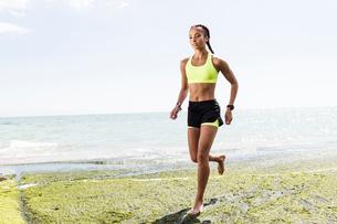 Young woman running, barefoot, beside seaの写真素材 [FYI03596304]