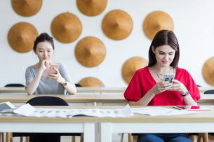 Students using mobile phone while waiting in classの写真素材 [FYI03596324]