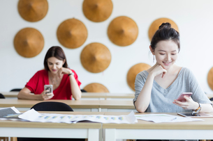 Students using mobile phone while waiting in classの写真素材 [FYI03596325]