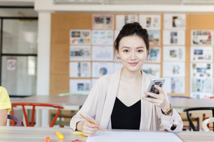 Student working using mobile phone in classの写真素材 [FYI03596328]