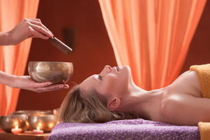Woman in spa environment, having relaxation treatment, therapist holding Tibetan bowlの写真素材 [FYI03596516]