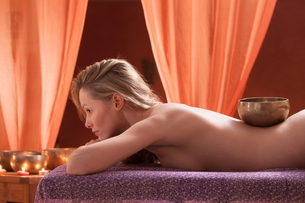 Woman in spa environment, having relaxation treatment, Tibetan bowl on her backの写真素材 [FYI03596531]