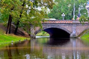 ラトビア・首都リガのダウガヴァ川を巡る観光船から見た緑の木々の映り込みと橋脚のある景観の写真素材 [FYI03596563]
