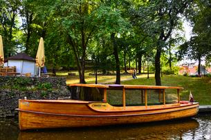 ラトビア・首都リガのダウガヴァ川を巡る観光船から見た緑の木々と観光船のある景観の写真素材 [FYI03596643]