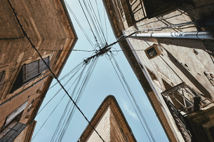 Low angle view of traditional buildings and power lines against blue sky, Pezenas, Occitanie region,の写真素材 [FYI03596663]
