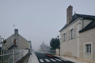 Taillight trail on road through Meigne-le-Vicomte village on misty morning, Loire Valley, Franceの写真素材 [FYI03596678]