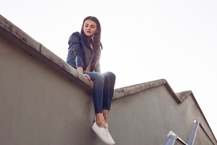 Young woman sitting on roof, low angle viewの写真素材 [FYI03596743]