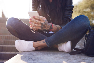 Young woman sitting on wall, using smartphone, tattoos on hand, low sectionの写真素材 [FYI03596748]