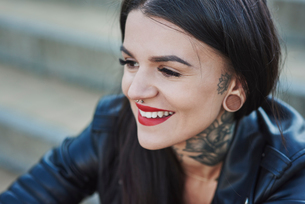 Portrait of young woman smiling, tattoos on neck, nose and ear piercings, close-upの写真素材 [FYI03596750]