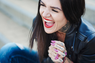Portrait of young woman laughing, tattoos on neck and handの写真素材 [FYI03596751]