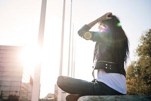 Young woman sitting cross-legged on wall, facing sunlight, tattoos on handの写真素材 [FYI03596752]