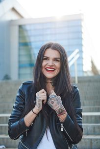 Portrait of young woman holding collars of jacket, smiling, tattoos on handsの写真素材 [FYI03596753]