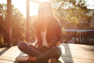 Young woman sitting cross-legged on wooden decking, looking way, smilingの写真素材 [FYI03596754]