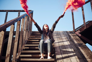 Young woman sitting on wooden steps, holding hand flares, red smoke pouring from flares, low angle vの写真素材 [FYI03596758]