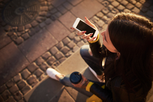 Young woman sitting outdoors, holding coffee cup, using smartphone, tattoos on hands, elevated viewの写真素材 [FYI03596760]