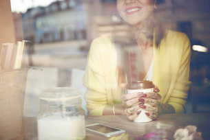 Young woman sitting in cafe, holding coffee cup, tattoos on hand, view through cafe window, mid sectの写真素材 [FYI03596761]