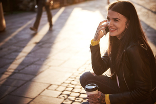 Young woman sitting outdoors, holding coffee cup, using smartphone, tattoos on handsの写真素材 [FYI03596764]
