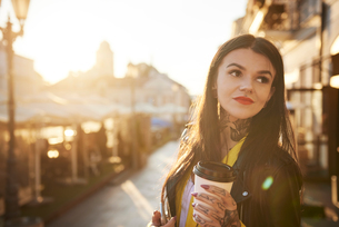 Young woman outdoors, holding coffee cup, tattoos on hands and neckの写真素材 [FYI03596765]