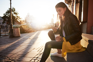 Young woman outdoors, holding coffee cup and smartphone, tattoos on handsの写真素材 [FYI03596766]