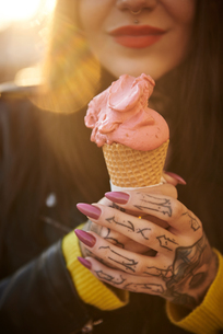 Young woman holding ice cream, tattoos on hand, mid section, close-upの写真素材 [FYI03596769]
