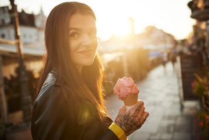Portrait of young woman holding ice cream, tattoos on handの写真素材 [FYI03596770]