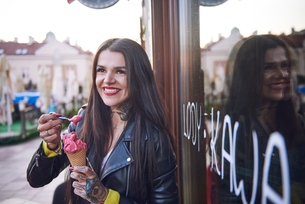 Portrait of young woman eating ice cream, tattoos on handの写真素材 [FYI03596771]