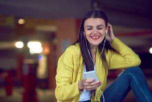 Young woman holding smartphone, wearing earphones, smilingの写真素材 [FYI03596774]