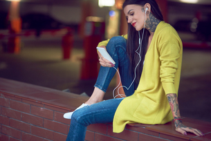 Young woman holding smartphone, wearing earphones, smiling, tattoos on hand arm, hand and neckの写真素材 [FYI03596775]