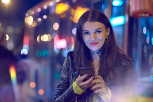 Young woman outdoors at night, holding smartphone, tattoos on hand and neckの写真素材 [FYI03596776]