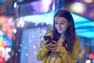 Young woman outdoors at night, using smartphone, tattoos on hands and neckの写真素材 [FYI03596777]
