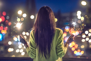 Young woman outdoors at night, holding lit sparklers, tattoos on hands, rear viewの写真素材 [FYI03596779]
