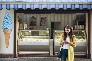 Young woman, outside ice cream parlour, using smartphoneの写真素材 [FYI03596780]