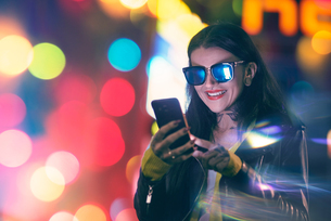 Young woman, outdoors at night, using smartphone, smilingの写真素材 [FYI03596781]