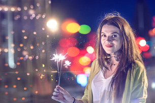 Portrait of young woman, outdoors at night, holding lip sparklersの写真素材 [FYI03596783]
