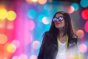 Portrait of young woman, outdoors at night, lights reflected in glassesの写真素材 [FYI03596784]